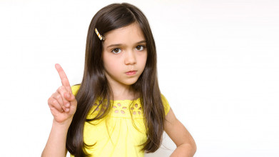 Serious-looking young girl in yellow dress pointing her finger in the air, like she's wagging it in disapproval