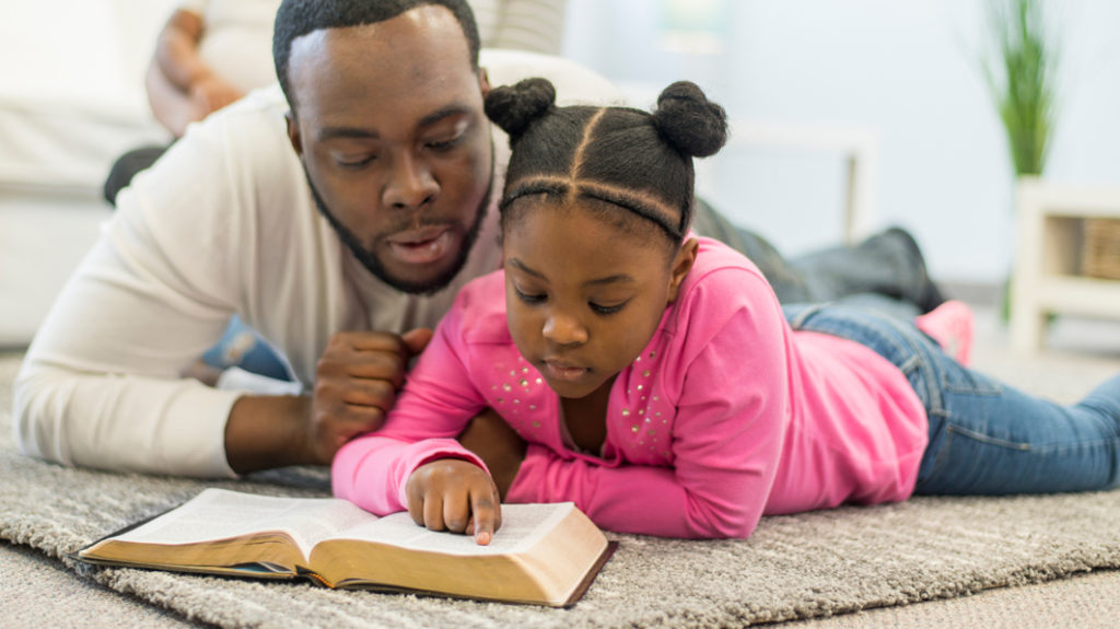 Father lying on the floor with his young daughter as she reads the Bible