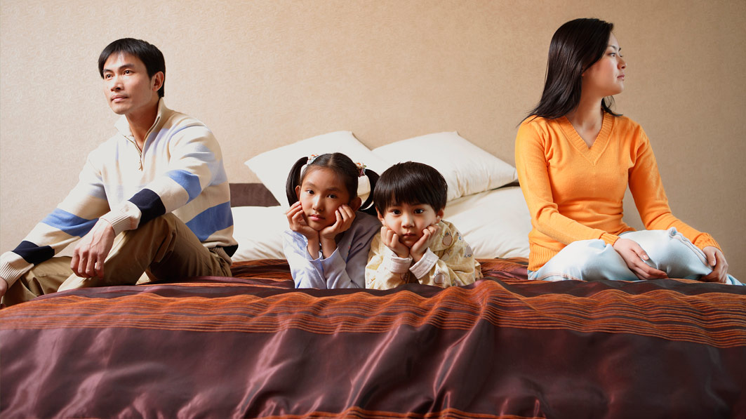 Serious-looking family sitting on large bed, with the couple sitting on opposite ends and two young kids lying in the middle