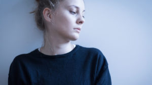 Somber woman staring at something off camera against a gray background