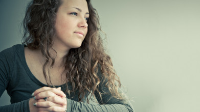 A young woman sits at a table with her hands folded atop a Bible as she looks reflectively to her left