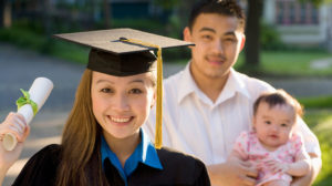 A smiling college graduate holding up her new degree, her husband cradling their baby in the background