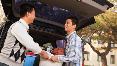 Adult child unloading car to move back home with parents