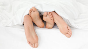 A couple's bare feet poking out from under the covers