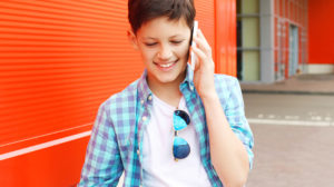 A young boy talks on his phone in the city