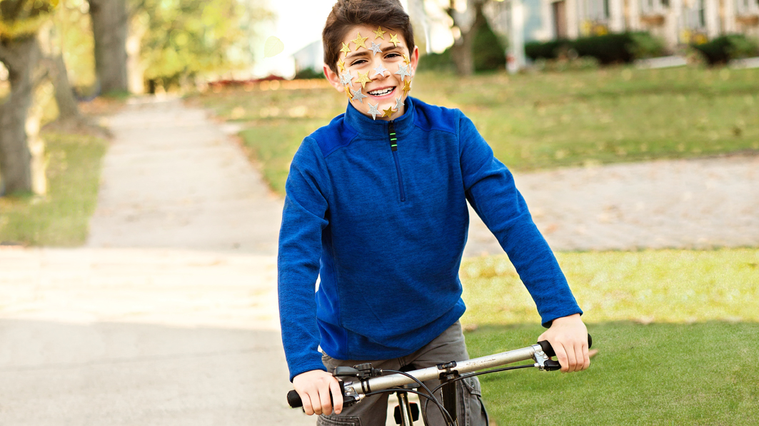 Healthy identity as seen by a smiling boy on a bike with star stickers on his face