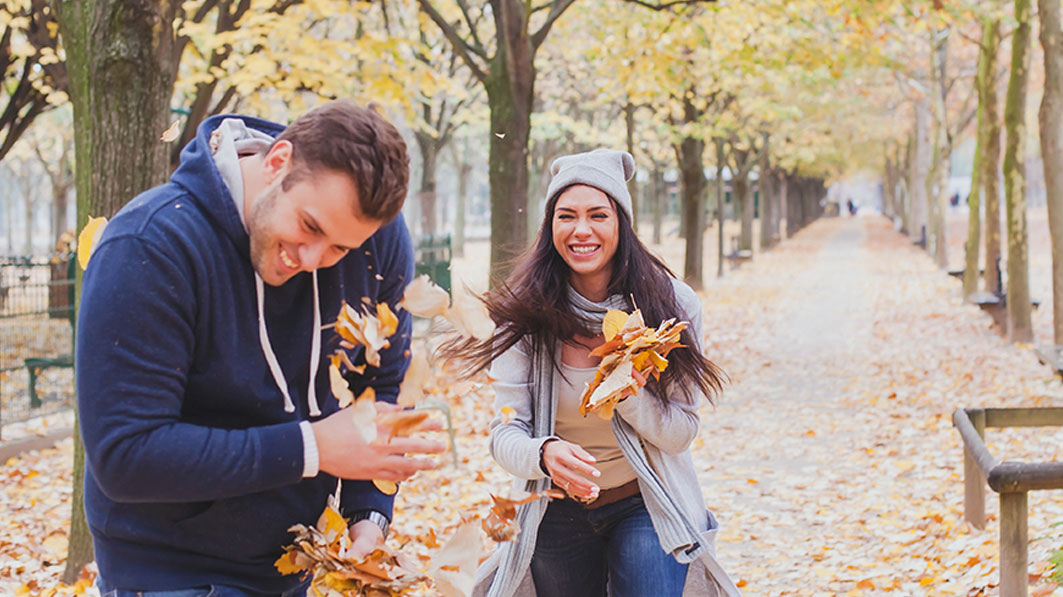 Couple laughing and playing as she throws fallen tree leaves at him on an Autumn day in the park