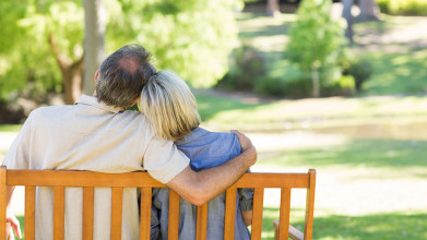 Shown from behind, a middle-age husband and wife sitting on a park bench. He has his arm around her.