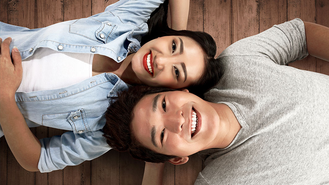 Happy couple lie close together on floor