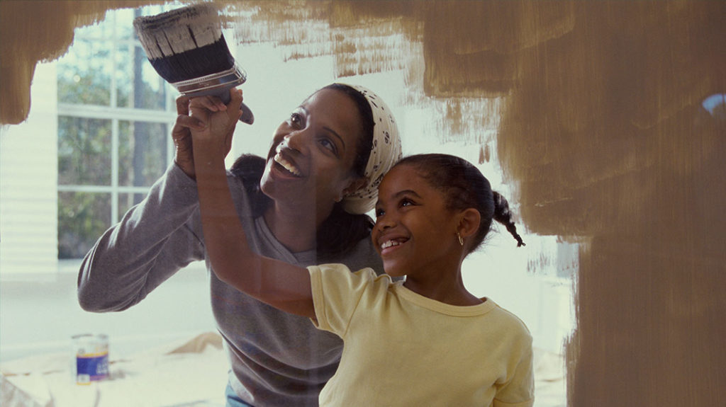 Mother and daugher painting a wall together