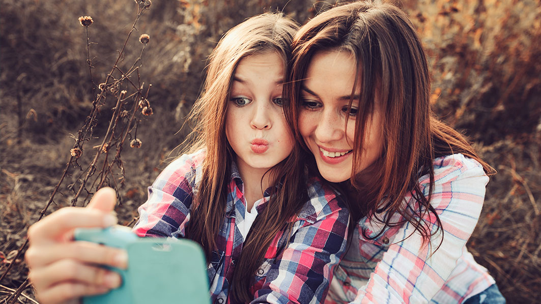 Mother and daughter taking selfies together