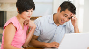 Husband and wife work through financial issues together on computer