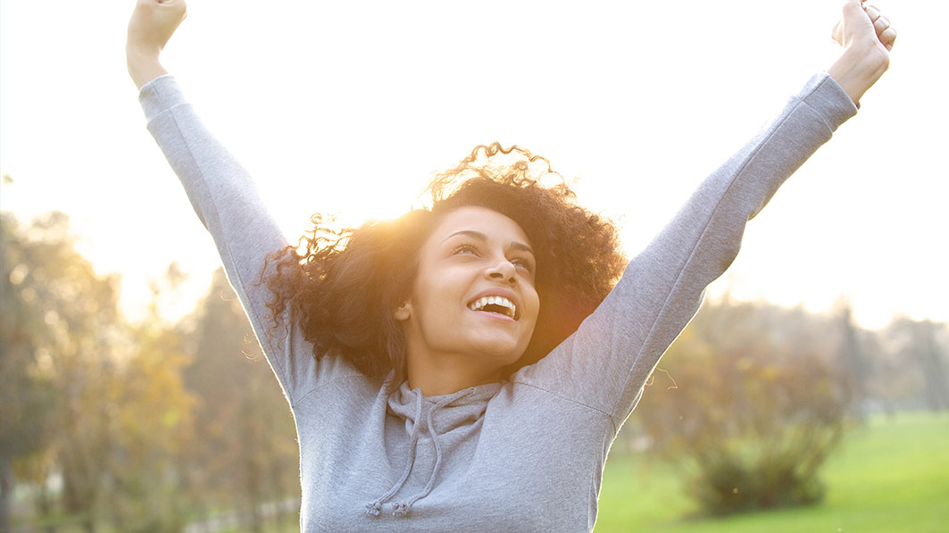 Joyful woman standing outside, raising her arms in the air as in victory