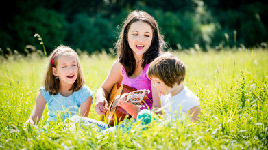 Mom playing guitar and singing with young daughters