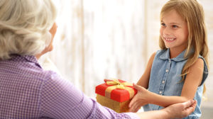 A granddaughter hands a wrapped package to her grandmother