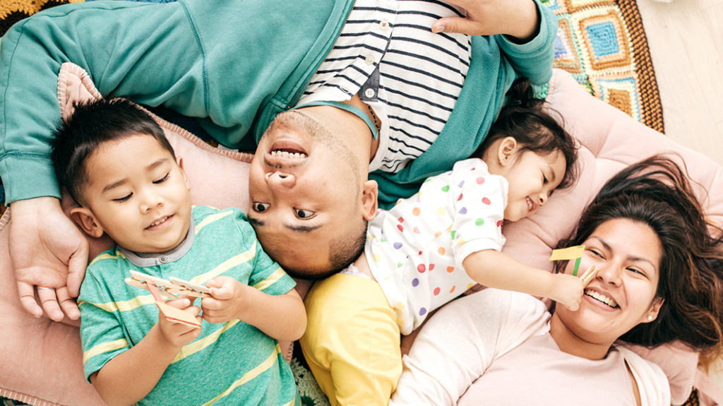 Shown from above, a joyful, playful family lying down; two young kids, a brother and sister, are playing with clothespins