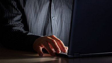 Close up of a man's hand typing on a laptop as he sits in the dark
