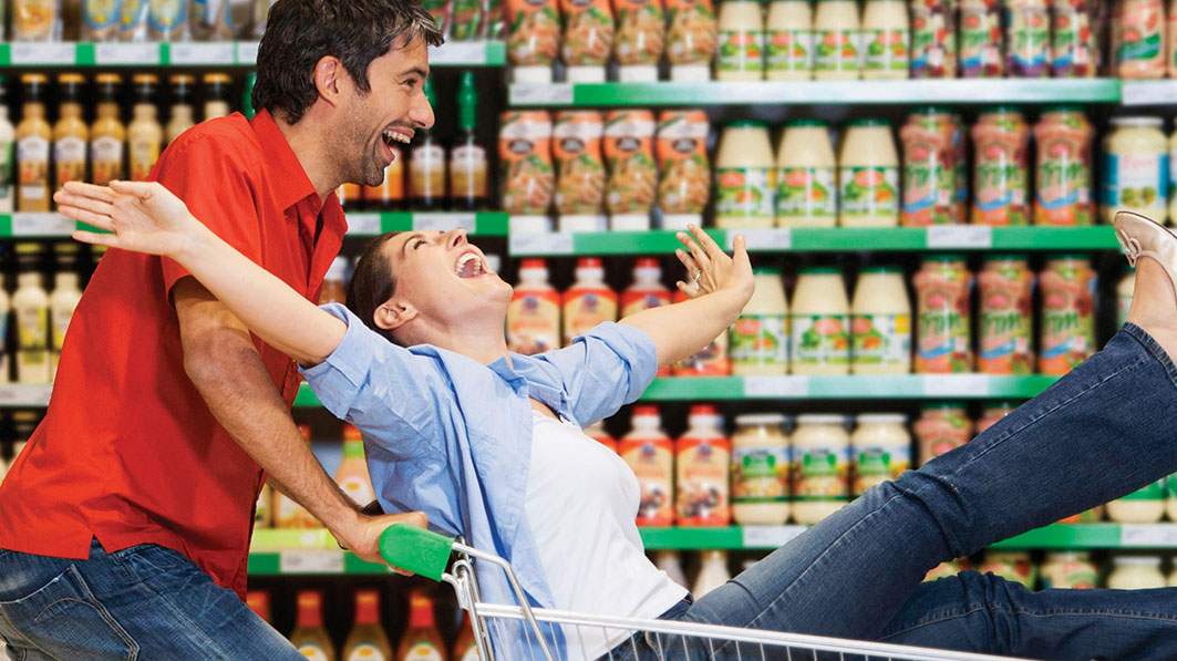 Husband and wife laugh as husband playfully pushes wife in cart inside grocery store