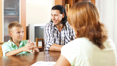 Mom and dad talk with teen at kitchen table