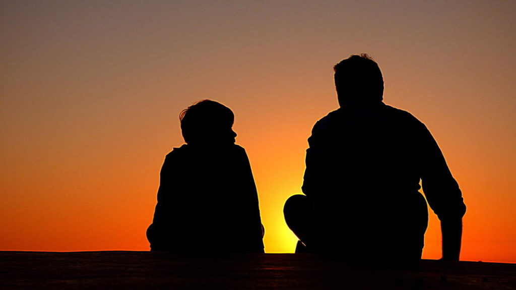 Silhouette of father talking with son with sunset in background