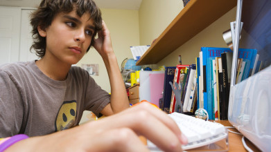 Serious-looking teen boy sitting at computer
