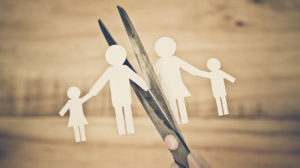 Paper cutout representing a family about to be cut in half with scissors