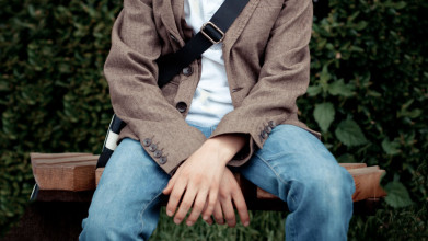 Young man sitting on a bench outside