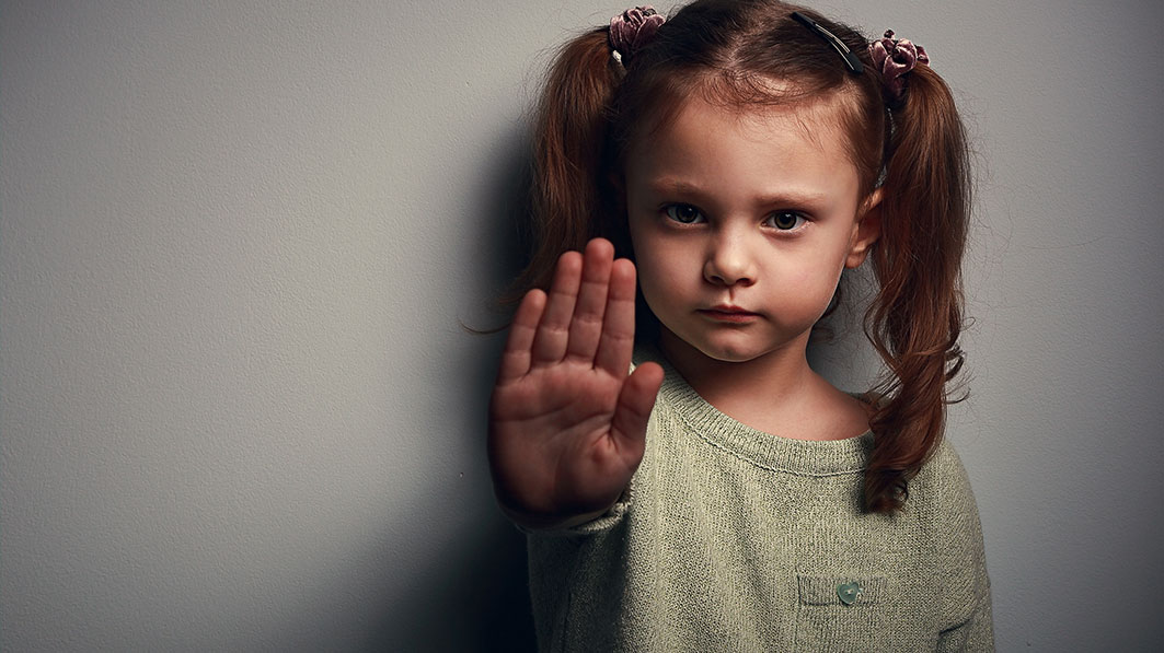 """Young girl holding up her hand to communicate """"stop"""""""