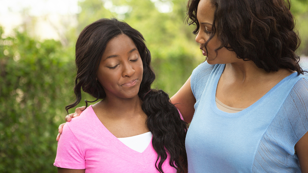 Mom with arm around her teen daughter, talking to her
