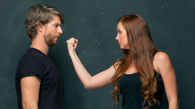 Angry woman threatening a man with her fist near his face
