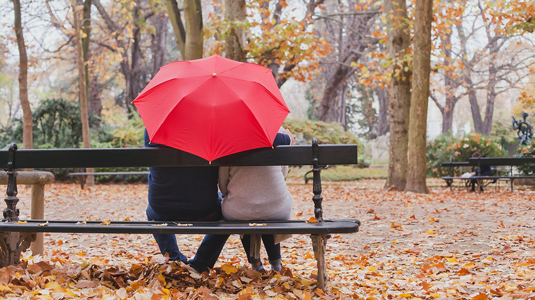 Shown from behind, a husband and wife sitting under an umbrella on a park bench on an autumn day