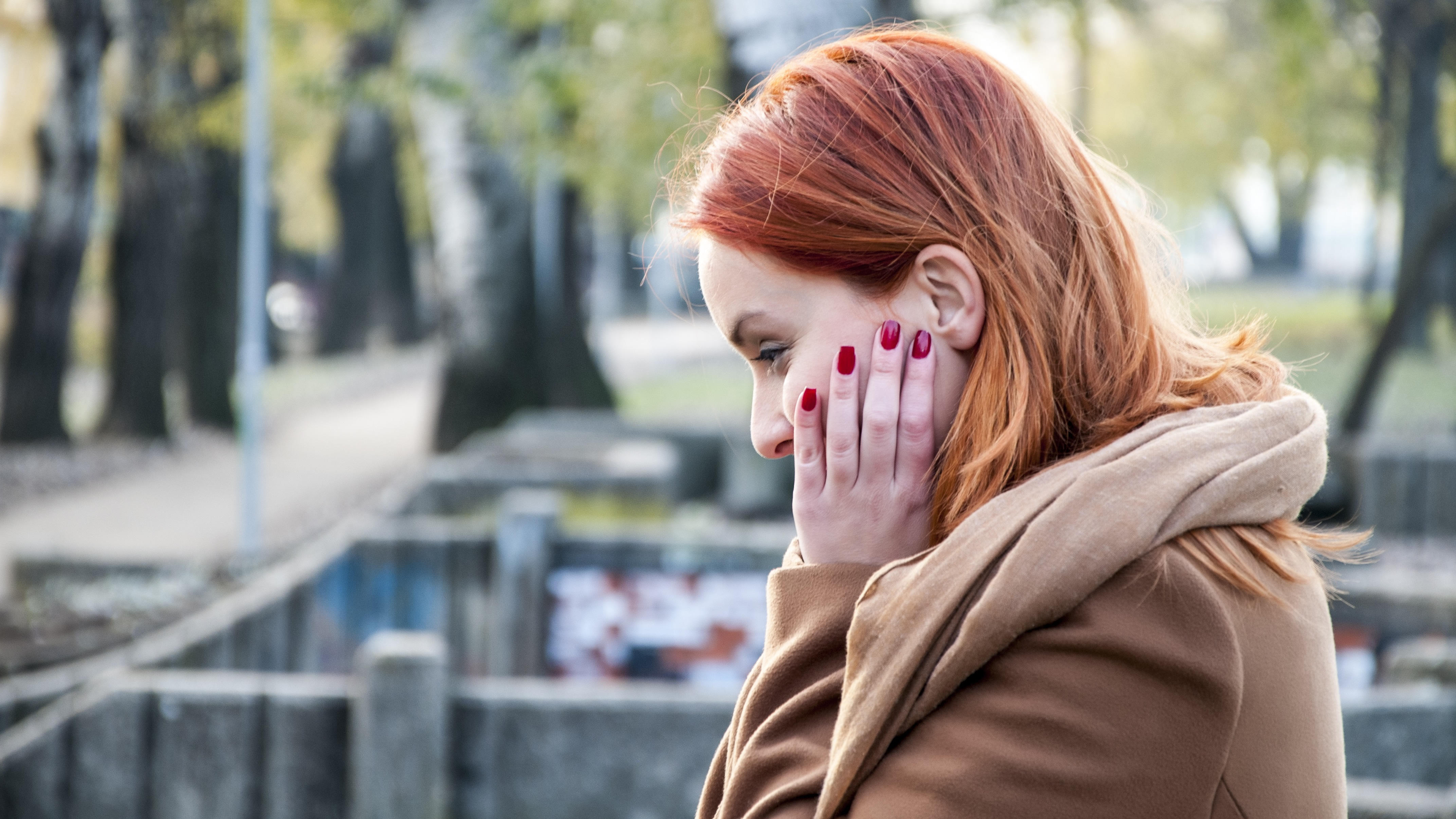 Profile of woman standing outside looking down pensively