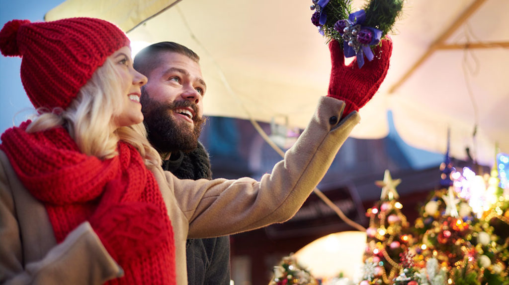 Happy young couple looking up at a Christmas decoration