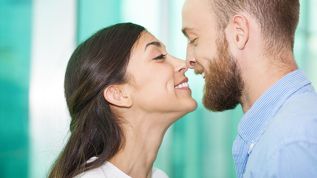Close up of young, smiling couple with their noses touching, like they're about to kiss
