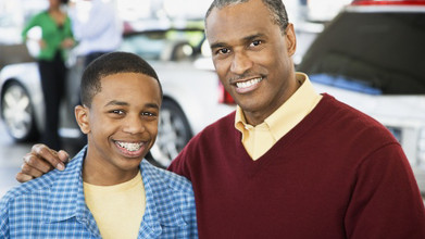 Smiling father and teen son posing for the camera, with a white car and two people in a blurred out background.