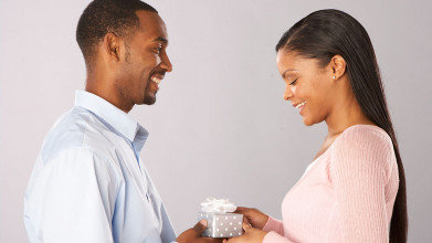 Close-up profile image of a smiling man handing a small wrapped present to a smiling woman
