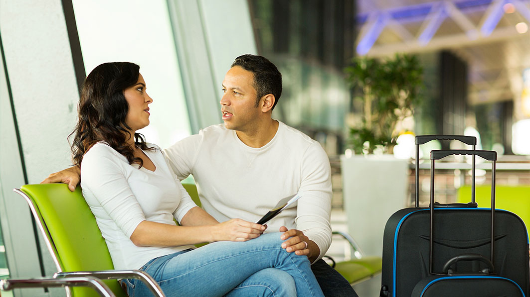 Couple sitting in an airport terminal having a serious conversation, their suitcases positioned next to them.