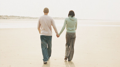 Shown from behind, a couple dressed for cool weather holding hands and walking down the beach.