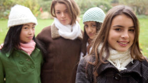 Four teen girls posing outside on a Fall day. One stands separately in the foreground smiling, the others look disapproving.
