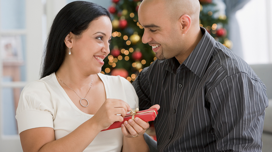 Smiling couple with Christmas tree in the background. She's about to open a small gift from him.