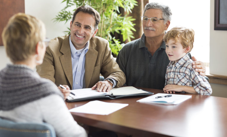 A Planned Giving Consultant smiles while speaking with grandparents and their grandchild
