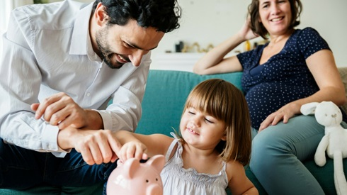 Father and young daughter putting money in a piggybank, with pregnant mom in the background
