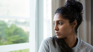 Serious looking woman staring out a window