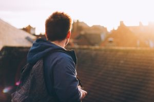 Young man with a backpack standing on a roof looking away from the camera over neighborhood rooftops