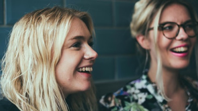 Close up of two young smiling blonde women looking at something to their left off camera