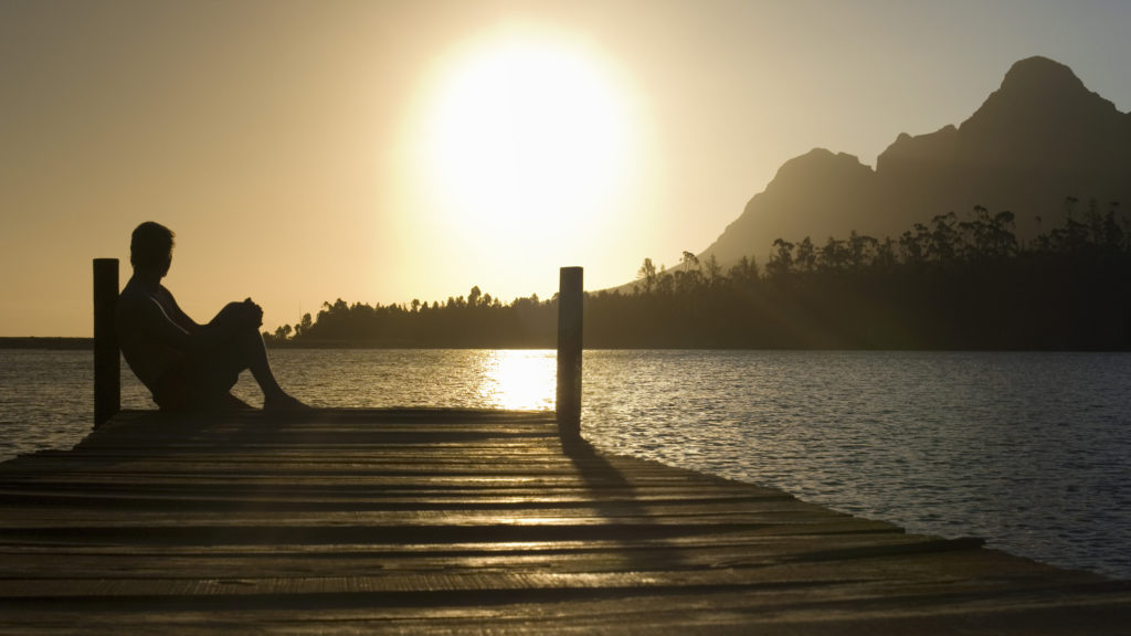 Silhouette of a man sitting on a dock looking out over a lake at sunset