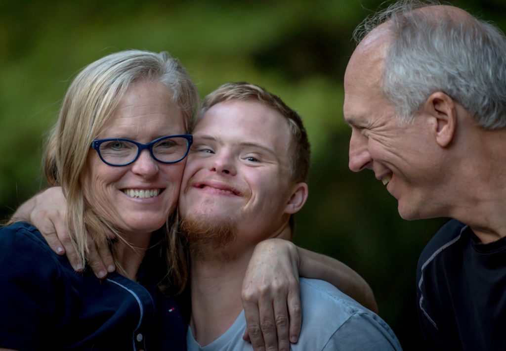 Close up of smiling middle-age couple with mom having a side hug with their grown, special needs son
