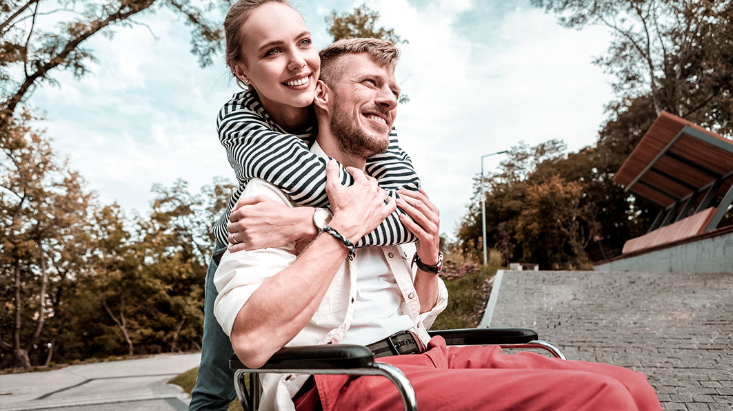 Disabled husband in wheelchair being hugged by his wife standing behind him. Both are smiling, and they are outside.