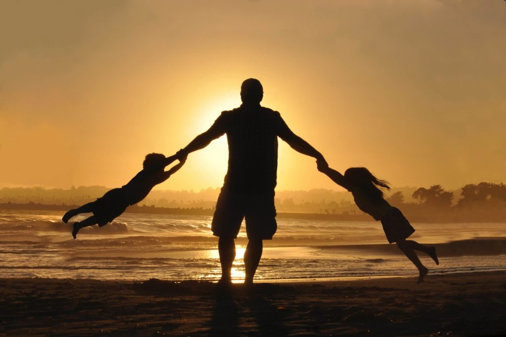 Silhouette of a dad spinning his two kids around on a lakeshore at sunset