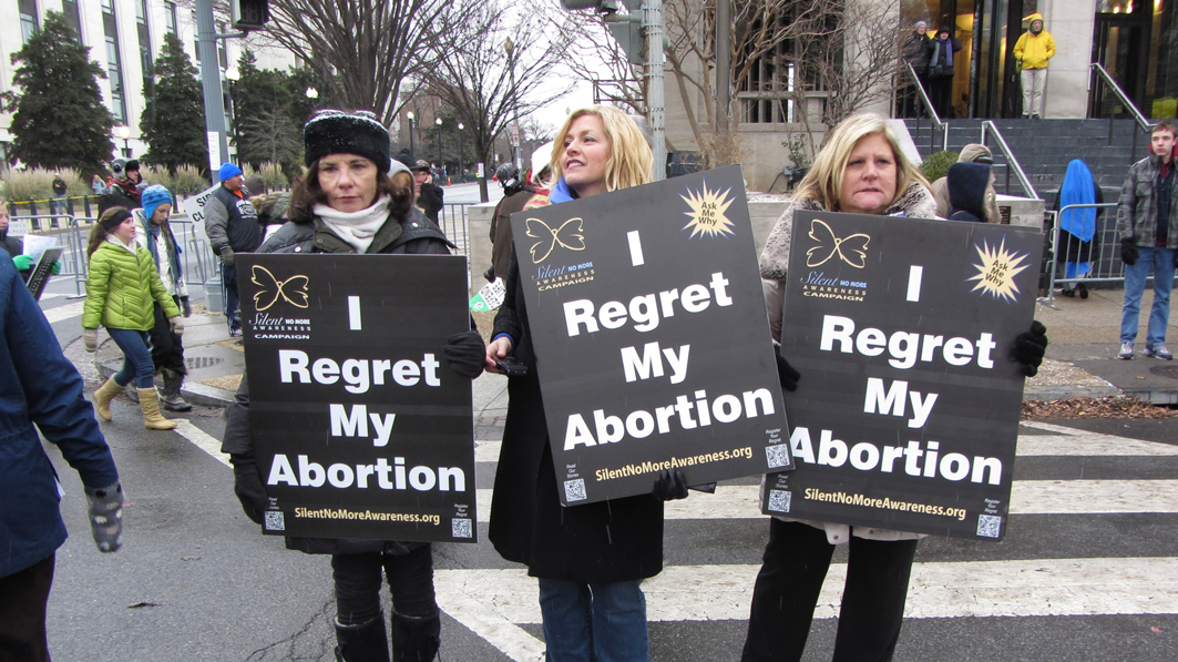 Three women at a pro-life rally near the Supreme Court holding signs that say they regret their abortion